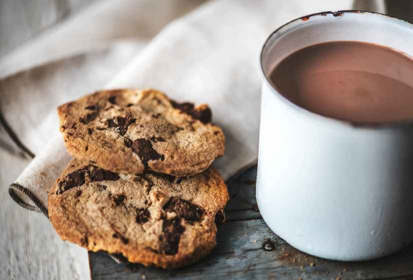 two cookies beside white metal mug